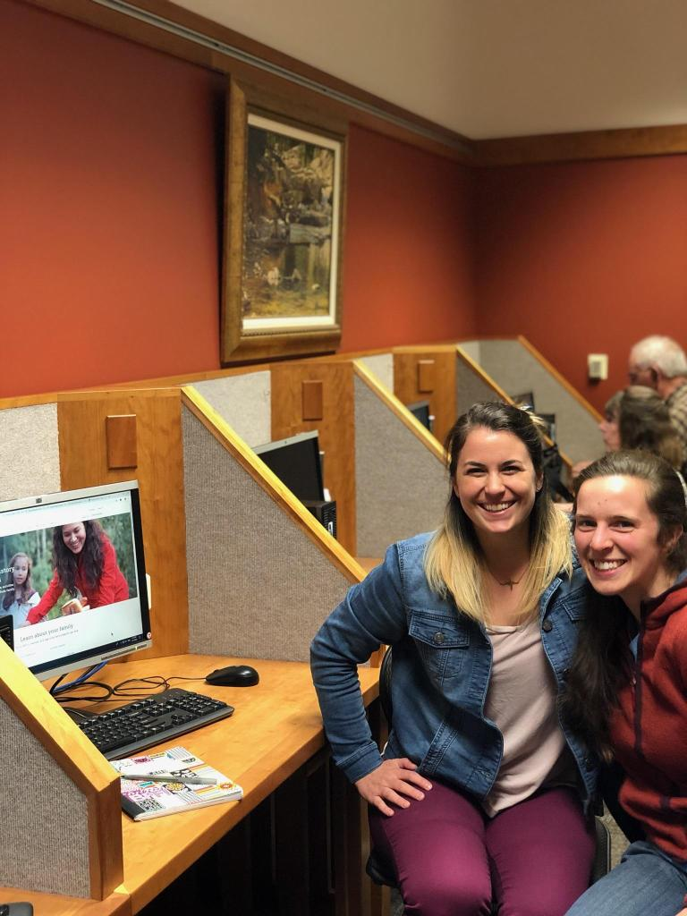 Two women smiling next to a computer during a family history consultation meeting. The woman on the right is Karynne Moses, owner of Moses Genealogy. The other is a client.